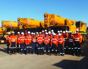 A group of labour workers for hire standing in front of cranes in Australia